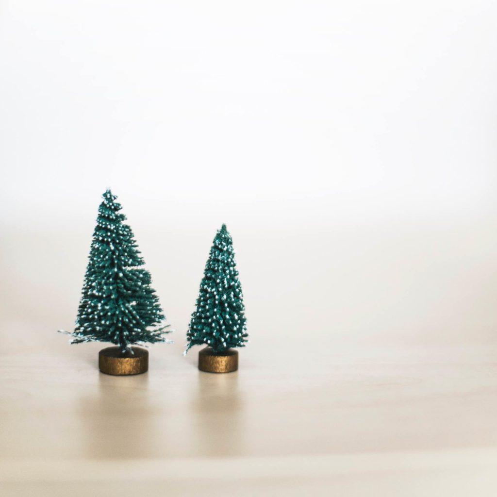 Zwei kleine Tannenbäume aus Plastik stehen vor einem beigen Hintergrund