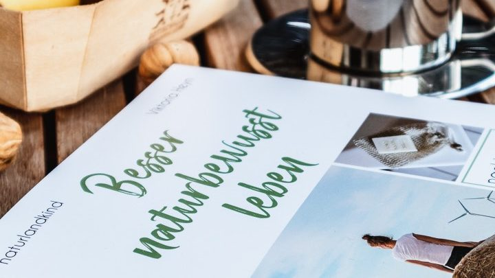 """Das Buch """"Besser naturbewusst leben"""" liegt neben einer Tasse Kaffee auf einem Tisch"""