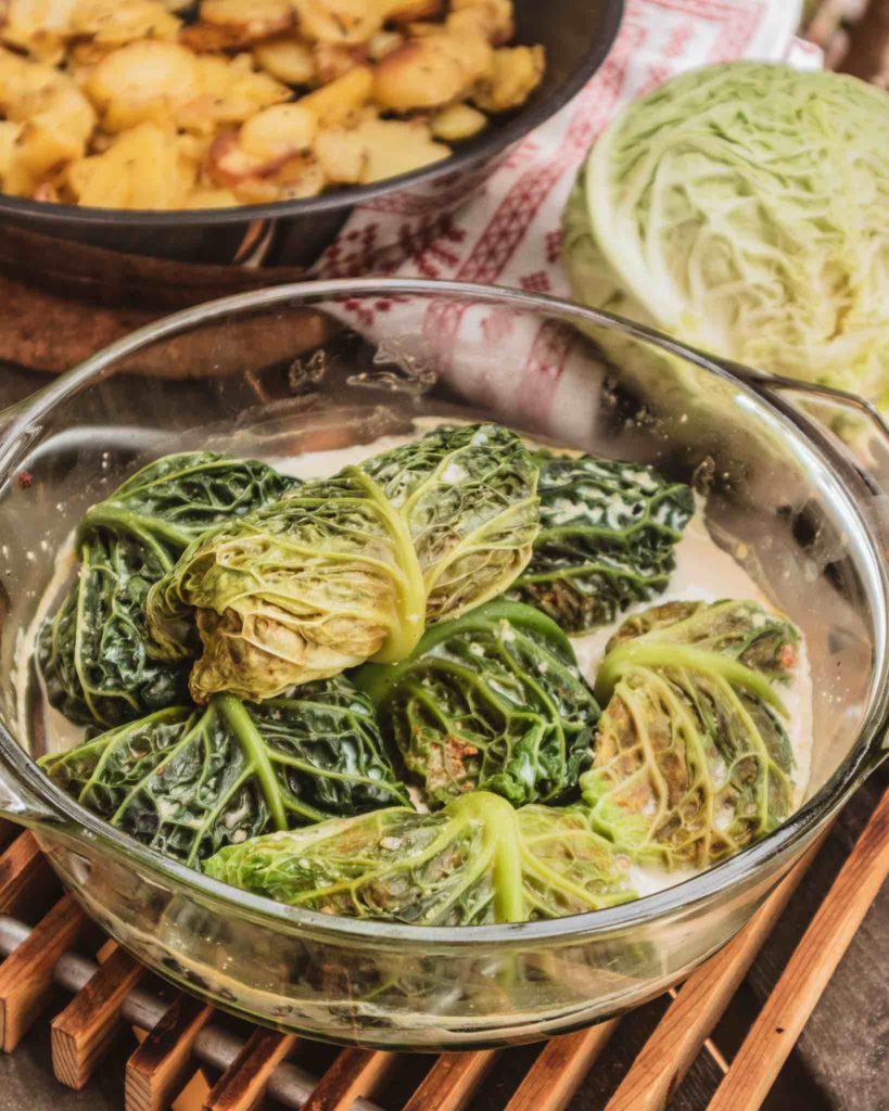 Vegane Wirsing Rouladen werden in einer Auflaufform gebraten. Dazu passen krosse Bratkartoffeln.